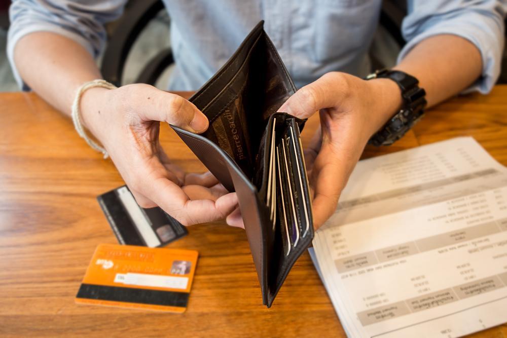 Mann sitzt mit geöffneter, leerer Brieftasche an einem Schreibtisch, auf dem Kreditkarten und Rechnungen liegen.