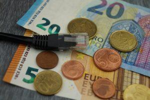 Verschiedene Geldscheine und Centstücke, auf denen ein Netzwerkkabel liegt.
